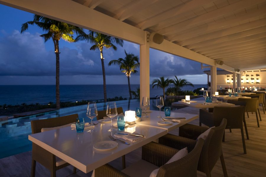 Poolside dining tables at restaurant Jarad at Le Toiny in St Barts with views of the Caribbean sea